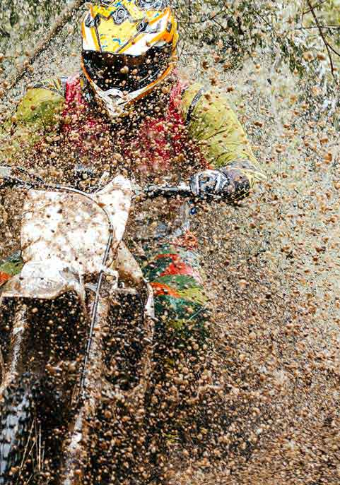 enduro rider riding dirt bike through water