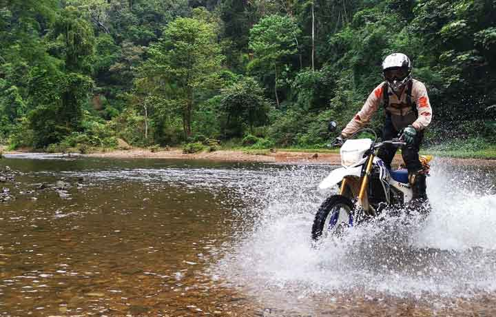 Professional Motorcycle rider riding a dirt bike through a big river fast