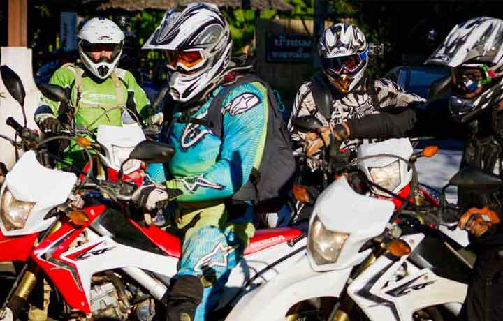 Group of dirt bike riders getting on their bikes in full riding gear in Burma