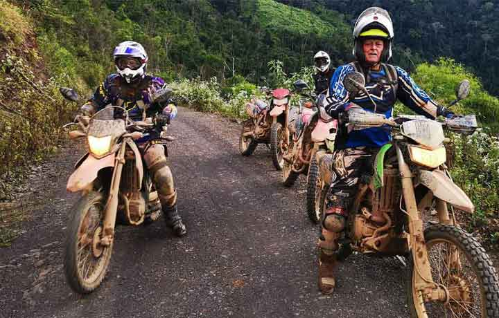 motorcycle tour group on dirty off road bike in Chiang Mai jungle