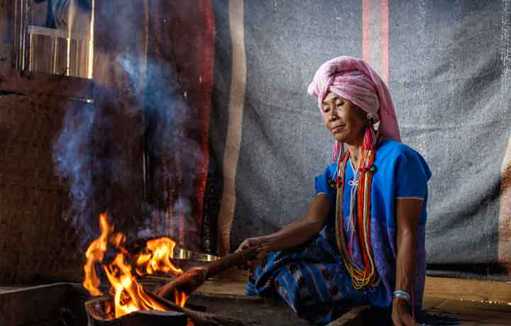 Old hill tribe lady sat by a fire inside a bamboo house in Northern Thailand